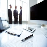 Business devices and documents at workplace, unrecognized businesspeople sharing ideas on background