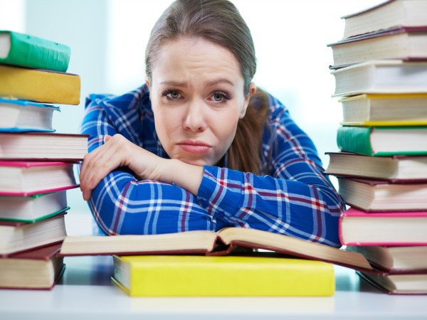 Portrait of a frustrated student being surrounded with piles of books